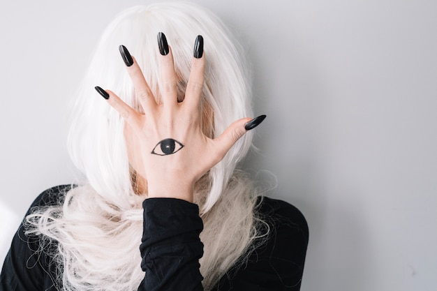Femme cachant le visage derrière la main avec un tatouage