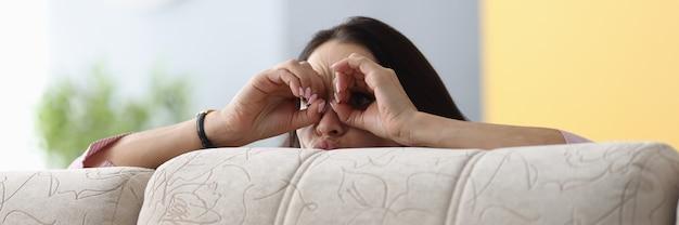 Femme cachée derrière un canapé et jette un coup d'œil à ses doigts à travers les jumelles sur son visage