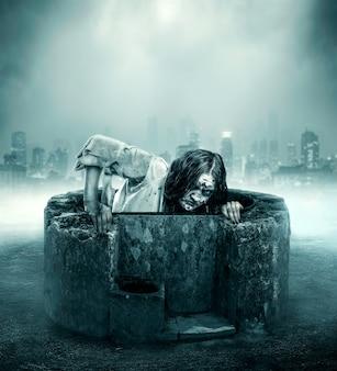 La femme cadavre sort d'un puits contre la ville
