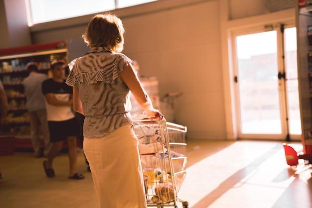 Femme avec un caddie dans le magasin d'alimentation