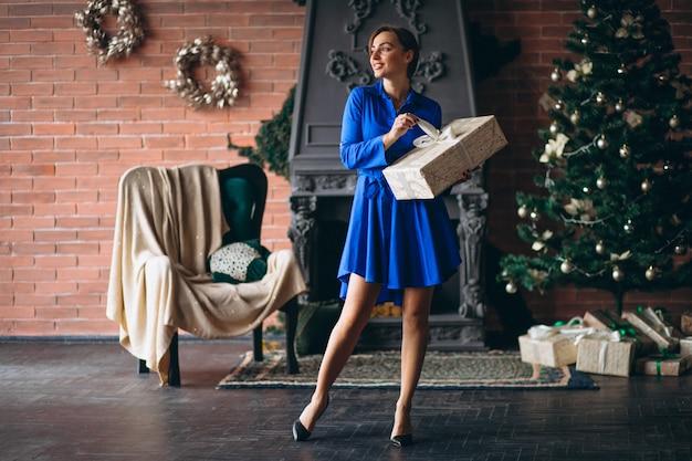 Femme avec des cadeaux et debout devant l'arbre de noël