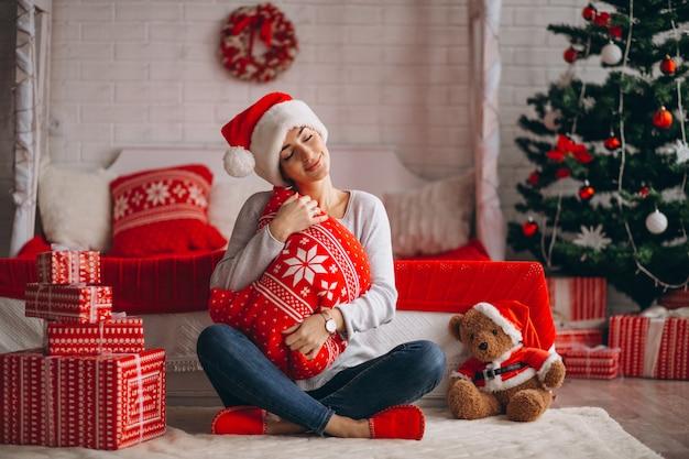 Femme avec des cadeaux de noël par sapin de noël