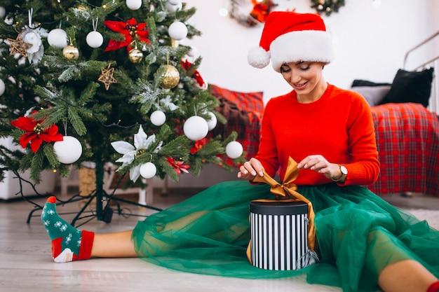 Femme avec des cadeaux par sapin de noël