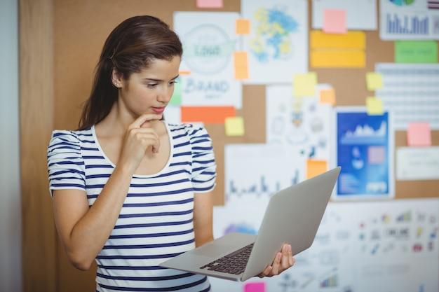 Femme cadre à l'aide d'un ordinateur portable au bureau