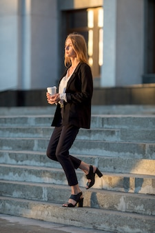 Femme avec café marchant dans les escaliers