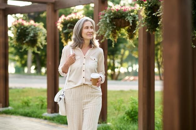 Femme avec café marchant dans un parc verdoyant