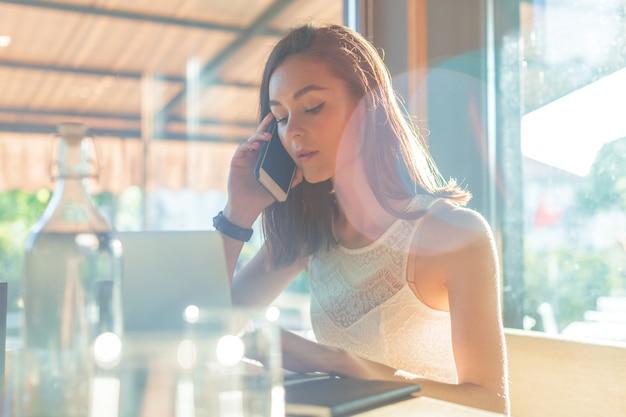 Femme à la cafétéria parle au téléphone