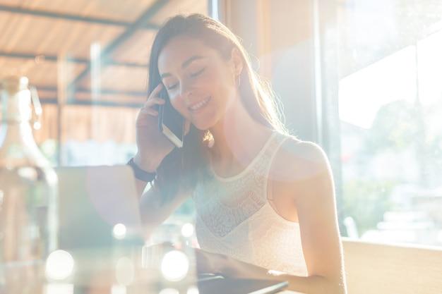 Femme à la cafétéria parler au téléphone