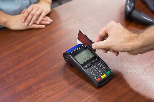 Femme à la caisse enregistreuse payant avec carte de crédit