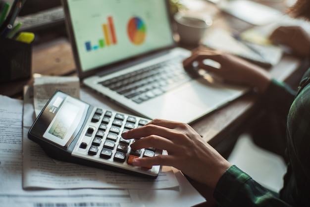 Une femme calcule le coût de la facture. elle appuie sur la calculatrice.