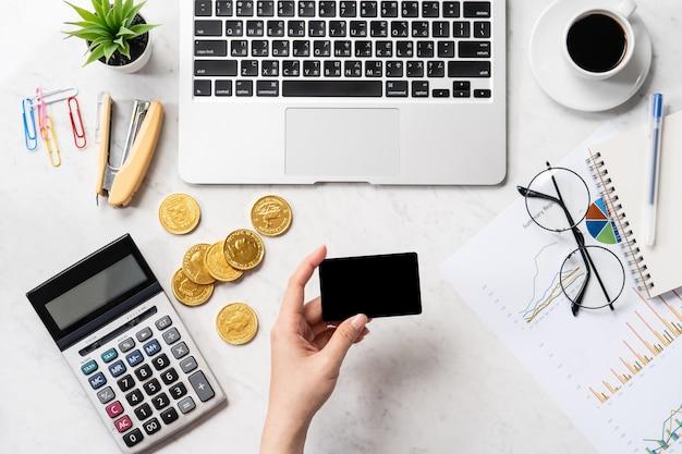 Une femme calcule les frais, les bénéfices et effectue un paiement en ligne sur une table de bureau en marbre moderne, maquette, vue de dessus, espace copie, mise à plat