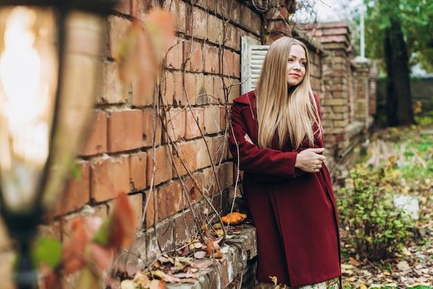 Femme calme blonde romantique portant un manteau en détournant les yeux et souriant tout en profitant de la confortable journée d'automne. fille posant pour la caméra