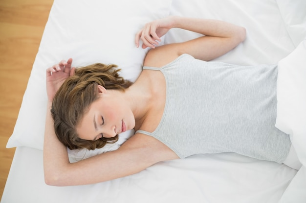 Femme calme dormant sous la couverture sur son lit