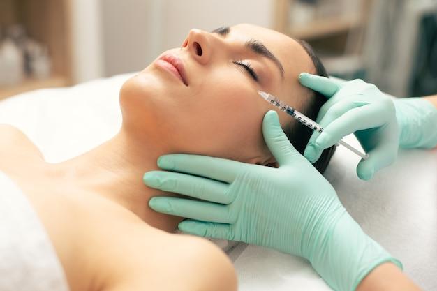 Femme calme étant au centre médical et ayant les yeux fermés tout en recevant une injection de vitamine dans la peau de son visage