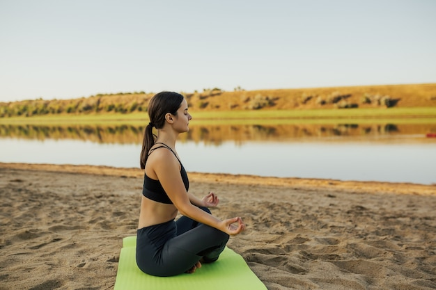 Femme calme méditant en yoga lotus sur la côte de la rivière sur la plage.