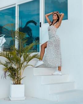 Femme calme positive en robe d'été légère, chapeau de paille, emplacement tropical