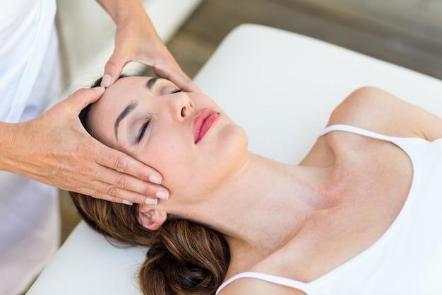 Femme calme recevant un traitement de reiki dans le spa de santé