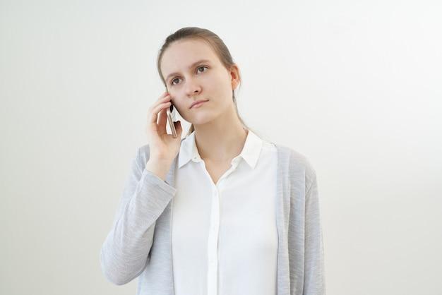 Une femme calme et sans émotion parle au téléphone, écoute une autre personne