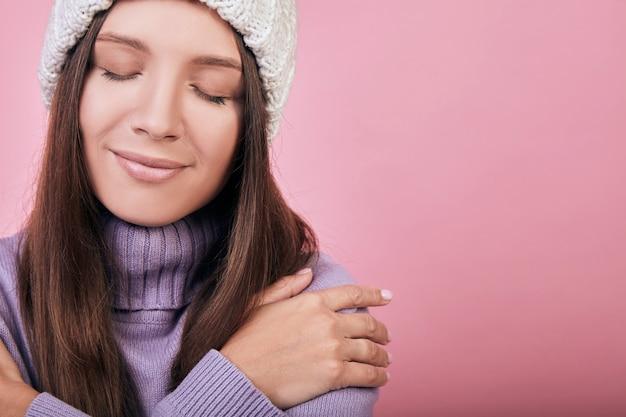 Une femme calme et souriante embrasse ses épaules, se réchauffe parce qu'elle est gelée