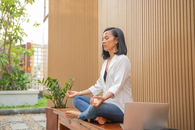 Femme calme avec les yeux fermés pratiquant le yoga en position du lotus