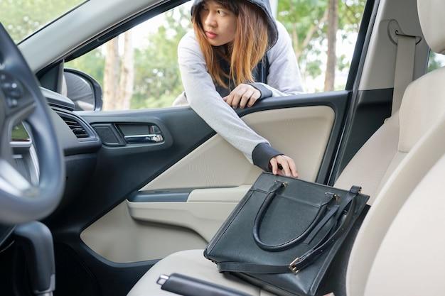 Femme cambrioleur voler un sac à bandoulière à travers la fenêtre de la voiture