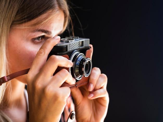 Femme avec caméra prenant des photos