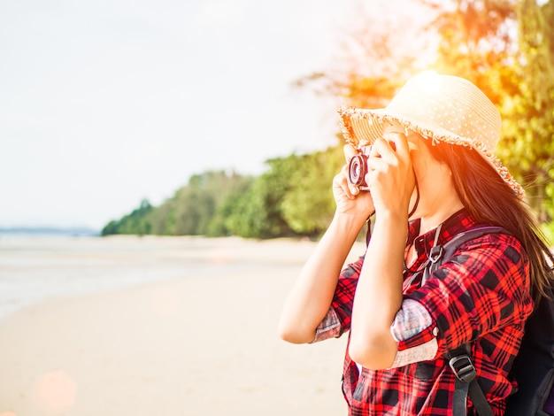 Femme avec caméra rétro hipster s'amuser à la plage.