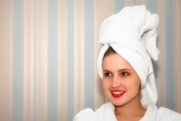 Femme sur le canapé de la chambre d'hôtel après la douche. jolie femelle d'apparence slave en robe de chambre et serviette sur la tête. heureuse dame. passer du temps en vacances. jolie fille après s'être lavée et montre des émotions