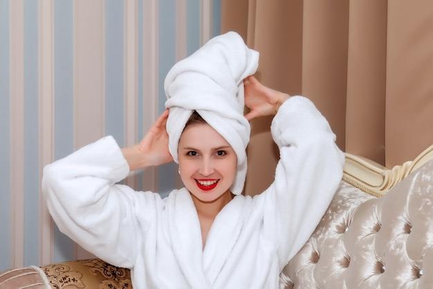 Femme sur le canapé de la chambre d'hôtel après la douche