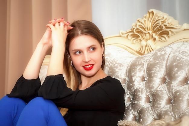 Femme sur le canapé de la chambre d'hôtel. jolie femme d'apparence slave en blouse noire et pantalon bleu. heureuse dame. passez du temps en vacances. jolie fille sourit et montre des émotions