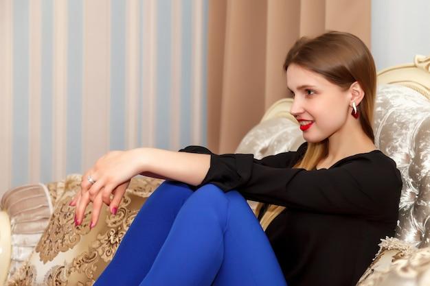 Femme sur le canapé de la chambre d'hôtel