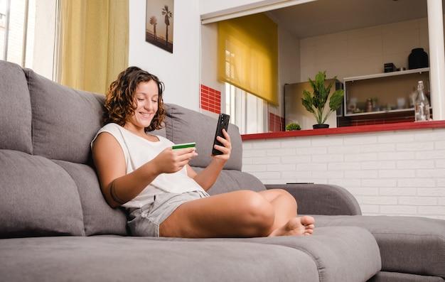 Femme sur le canapé du salon shopping en ligne avec une carte de crédit et un smartphone