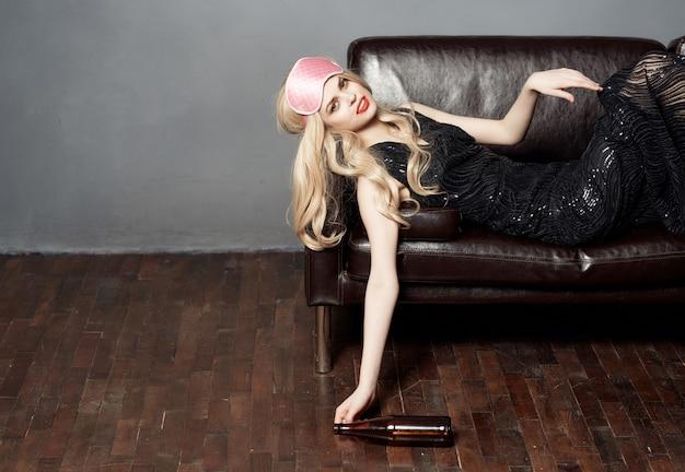 Femme sur le canapé enduit de rouge à lèvres vie nocturne bouteille d'alcool fond sombre