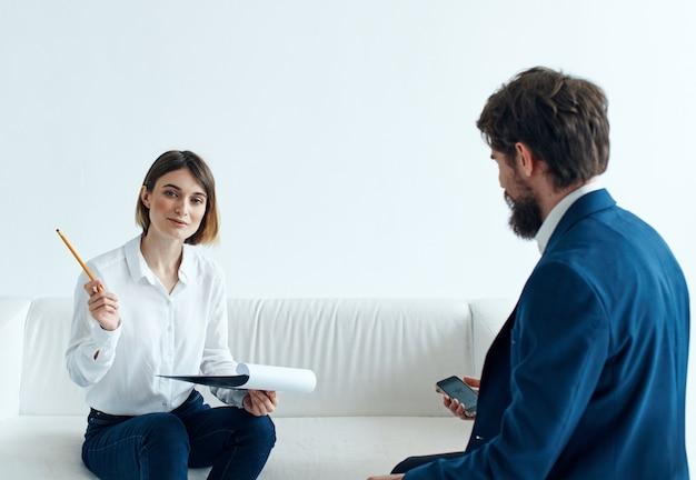 Femme sur canapé à l'intérieur psychologue communiquant et homme en costume.