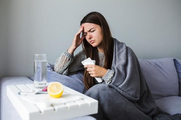 Femme sur un canapé avec des médicaments