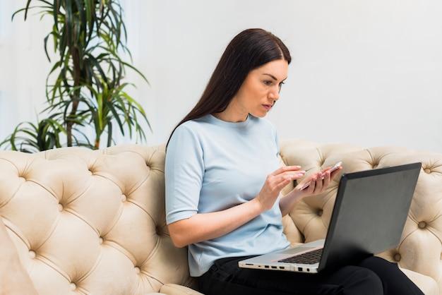 Femme sur un canapé avec un ordinateur portable à l'aide d'un smartphone