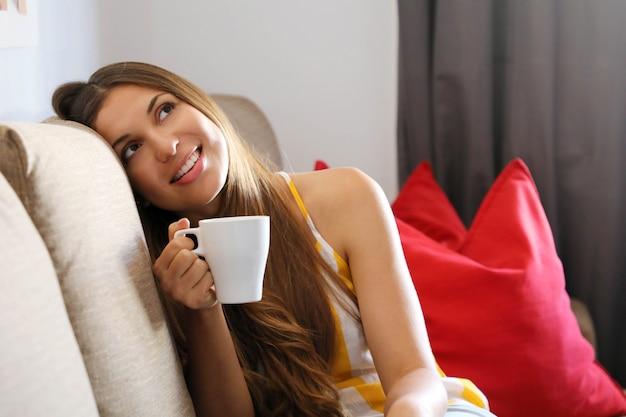 Femme sur canapé tenant une tasse de café