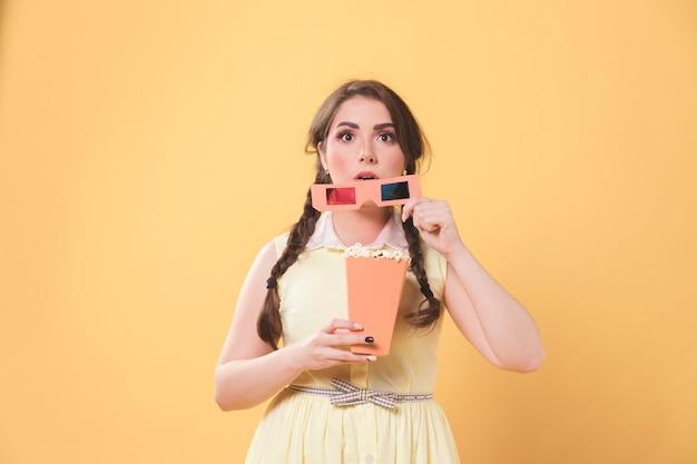Femme captivée tenant des lunettes de cinéma et du pop-corn