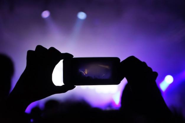Femme capturant un concert de rock en plein air vidéo
