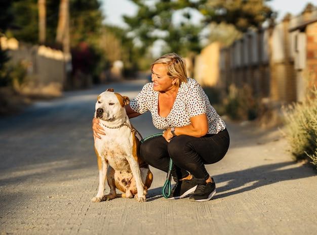 Femme caressant un chien assis dans une rue non pavée