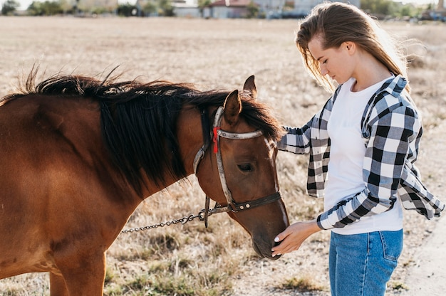 Femme caresser adorable cheval
