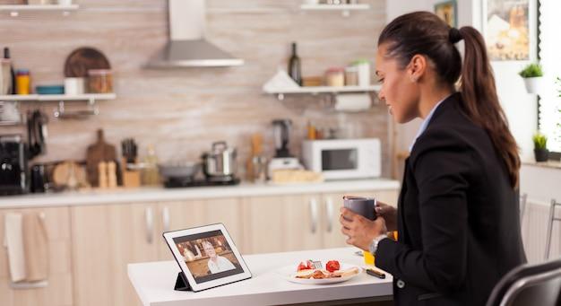 Femme de carrière parlant avec sa mère sur webcam pendant le petit-déjeuner