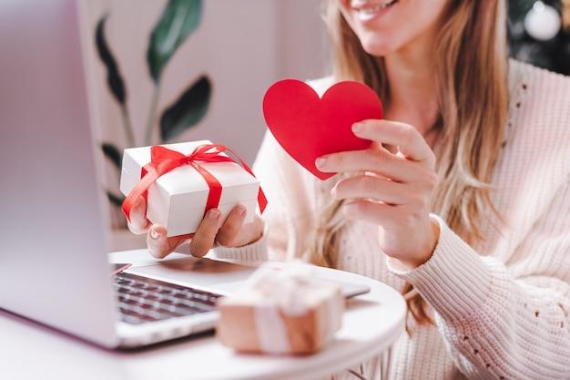 Femme avec carte de la saint-valentin et cadeau ayant un chat vidéo sur ordinateur portable