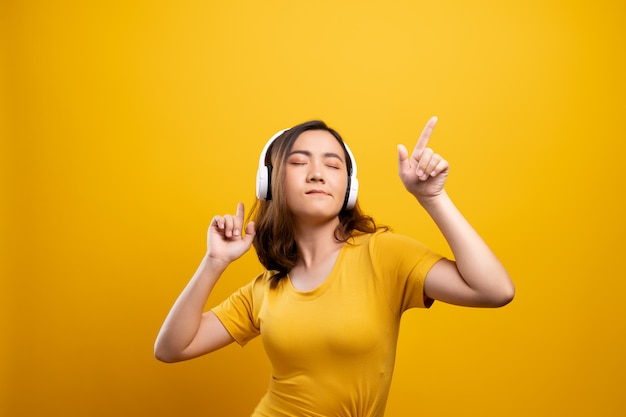Femme avec un casque d'écoute de musique sur fond jaune isolé