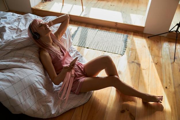 Une femme avec un casque écoute sa musique préférée en se penchant sur son lit à la maison