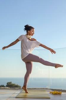Femme avec un casque faisant du fitness à la maison