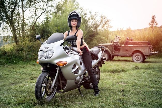 Femme avec casque à la main, debout près de la moto