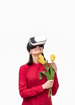 Femme avec casque de réalité virtuelle tenant des fleurs