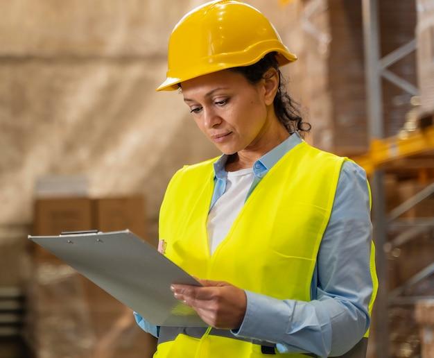 Femme avec casque travaillant dans l'entrepôt