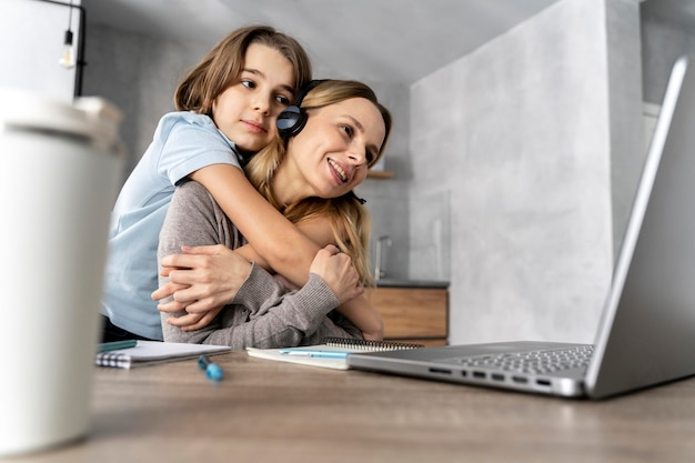 Femme avec casque travaillant sur un ordinateur portable étreint par une fille